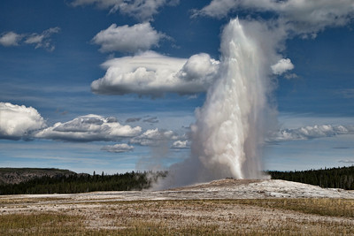Old Faithful in Yellowstone Park - Wyoming USA. Image processed with Topaz adjust 5 to add some color and detail to the image. At the time of the shot, the sky was cloudy with large dense Cumulus cloud that did not provide much light to the image. Topaz fixed that for me.