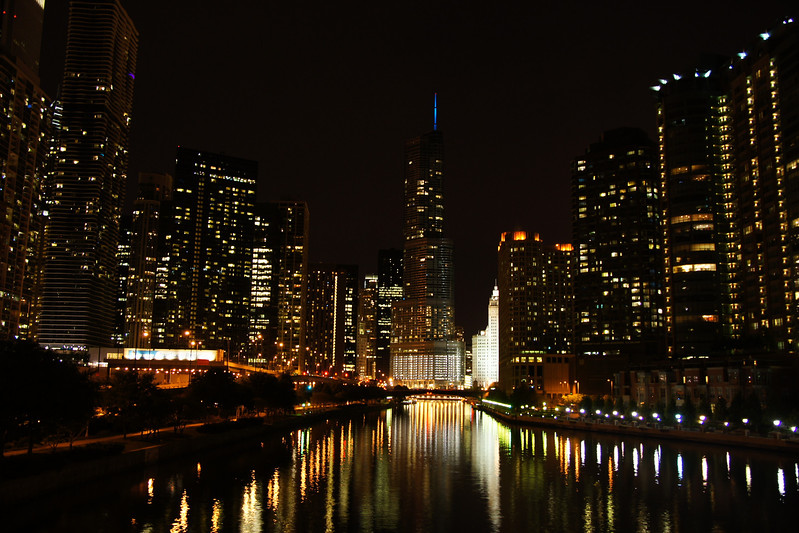This is a night travel photo showcasing the bright lights of huge skyscrapers and buildings in downtown Chicago late at night on a chilly fall evening - USA.