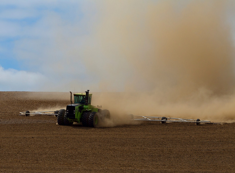 A Farmer cultivates his field preparing it for the next crop. Palouse region, Washington, USA.