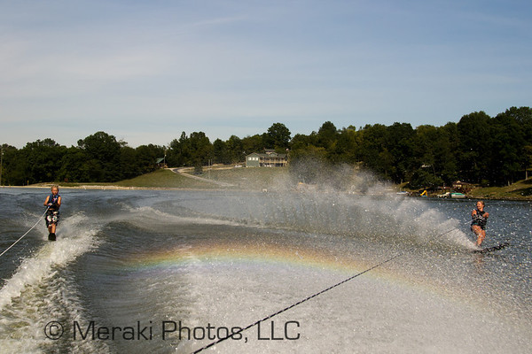 Photo of rainbow between two water skiers