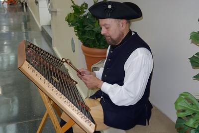 Historical interpretor playing a dulcimer
