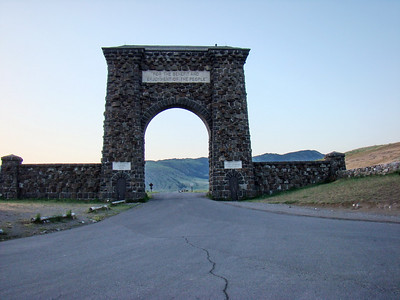 """Le """"fameux"""" porche de l'entrée nord. Il est 5h55! Roosevelt Arch - The Roosevelt Arch is located just outside of the town of Gardiner Montana. It is a reminder of the 1903 Trip that Teddy Roosevelt made to Yellowstone. This was once the main gateway into Yellowstone National Park due to the fact that the National Park Railroad once had a Park Line from Livingston Mt to Gardiner MT. A depot use to be located here and where the present day school is located was the turn around for the trains. At this point the passengers disinbarked from the train and loaded into the stagecoaches for the 5 mile trip up to Mammoth Hot Springs."""