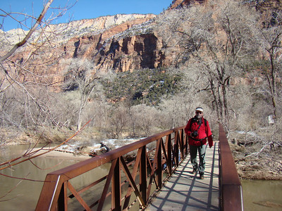 "Detailed Description: The Sand Bench Loop starts at the Court of the Patriarchs shuttle stop and is roughly 3.5 miles (round trip). From the shuttle stop, cross the main road and walk the access road to a large water tank and the hikers' bridge across the Virgin River. The trail initially heads west to offer a good view of the Court of the Patriarchs, then it heads south and crosses a small stream, then climbs to the top of the landslide. (From the Court of the Patriarchs, a small spur trail also heads north to connect with the Zion Lodge/Emerald Pools trailhead.) Total elevation gain up to the top of the sand bench is roughly 500 feet, much lower than any hikes to the canyon rims. Be sure to do the entire loop as both parts of the trail offer unique views. The eastern trail is more rocky with many interesting boulders scattered about and good views of the main canyon and the road below. The western loop of the trail offers amazing unobstructed views of the actual ancient landslide.  This trail sounds too good to be true, right? Well here's the downside: SAND. They don't call it the ""sand bench"" for nothing; much of the trail is fine sand, some of it quite deep which makes the going slow and miserable in some spots. To make things even more enticing, the Sand Bench Loop is the trail that is designated for guided horseback rides within the park, so during the peak season (usually April through October), you will have to watch out for ""steaming gifts"" and wet spots. As of 2005, there are typically two guided horseback tours a day, so at least you won't be completely inundated with passing horses. Because this trail is also quite hot and exposed, the best time to hike this trail is probably the cooler season: September to May."