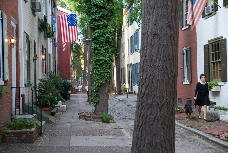 Woman walks her dog down Quince Street, one of the city's many old, narrow lanes, Philadelphia, PA.