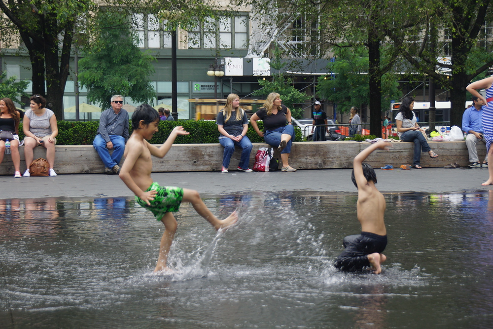 Children playing and splashing at Millennium Park in downtown Chicago