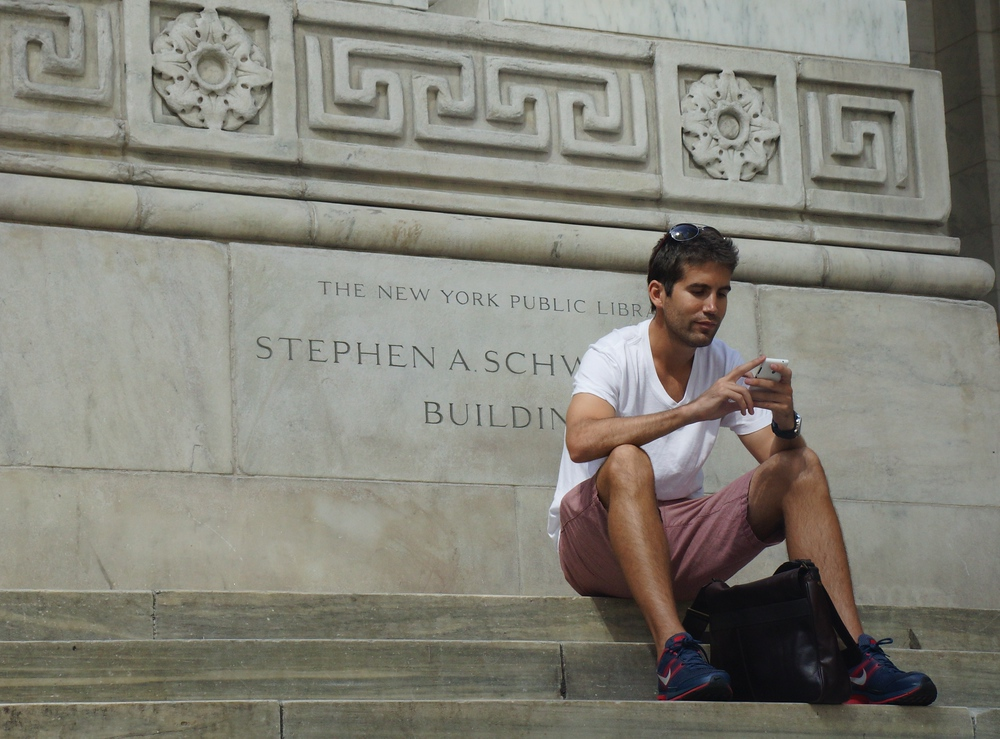 Man texting on his cellphone outside of the New York Public Library