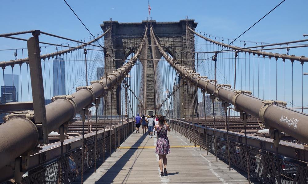 Audrey Berger 'That Backpacker' taking a photo walking along the Brooklyn Bridge in New York City