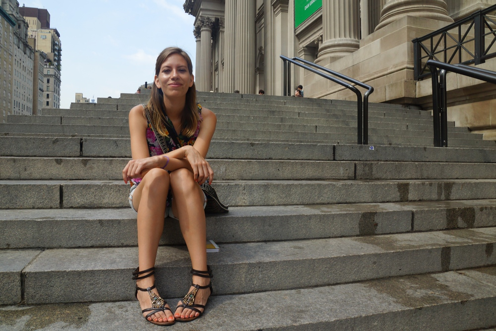 Audrey Bergner 'That Backpacker' sitting on the steps outside of the MET Museum in New York City
