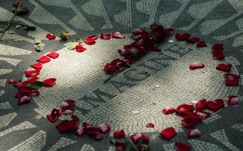 Flowers and flower petals outside of the John Lennon Strawberry Fields Imagine Memorial in Central Park New York City