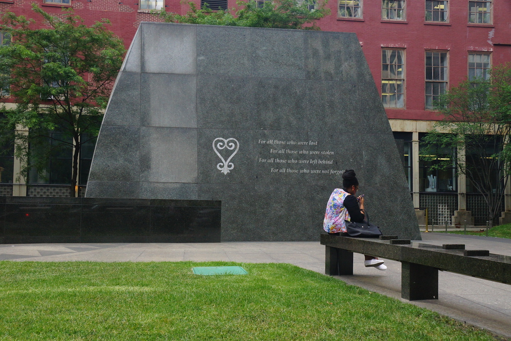 Lady city on a park bench outside of the African Burial Ground in New York City