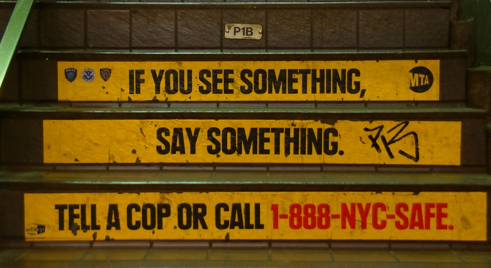 If you see something say something tell cop advertising on the steps of a New York City metro station
