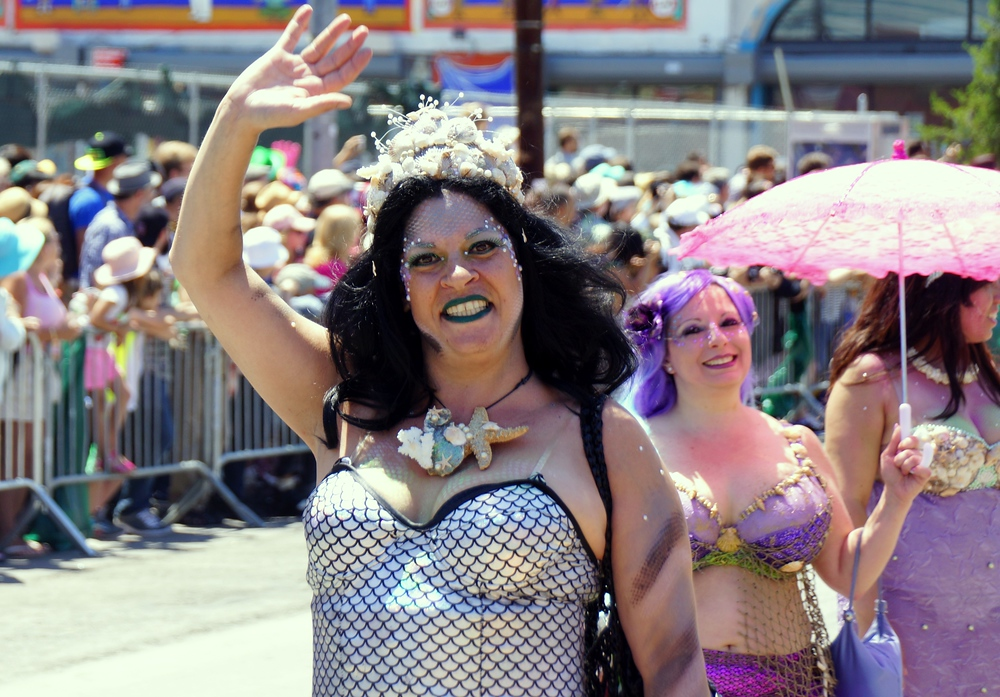 A performer in a Mermaid costume waving as she walks down the street in New York City