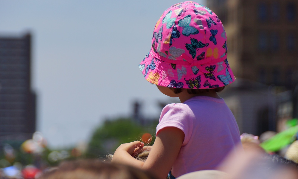 A little girl sitting on top of her Dad's shoulders watching the Coney Island Mermaid Parade.