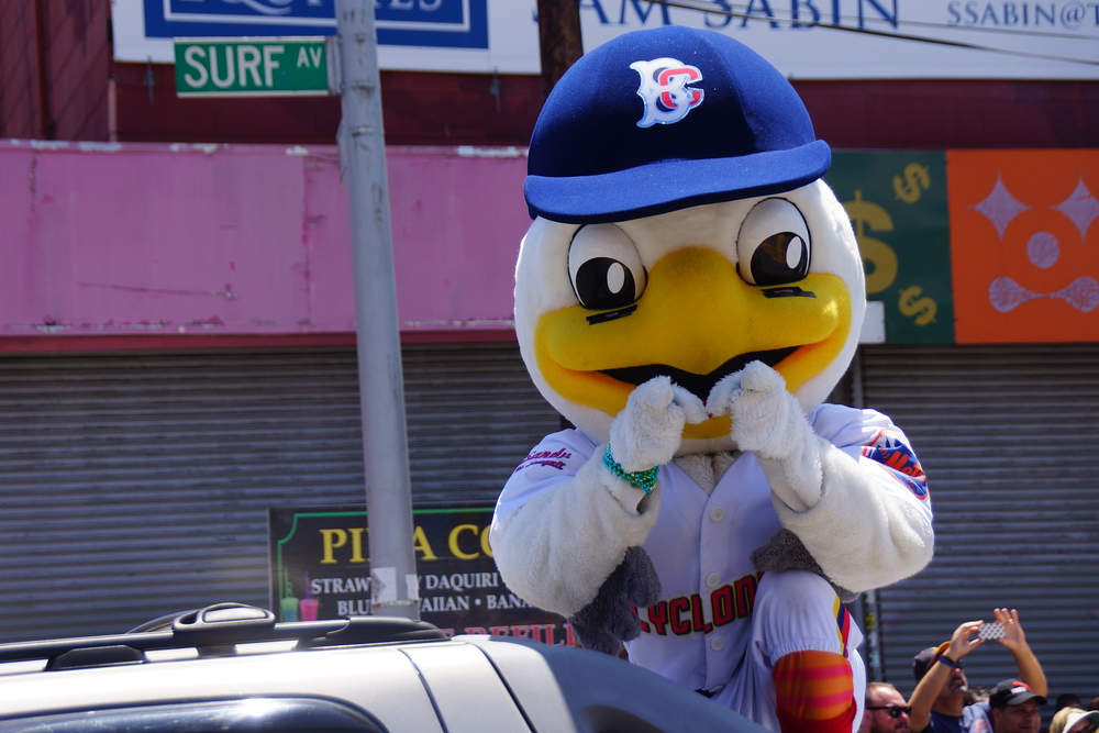 A New York City baseball mascot pointing at the crowd as it parades down the Coney Island Mermaid Parade.