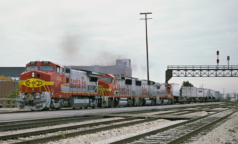 The engineer starts to open up Santa Fe B40-8W 544, GP60M 108, GP60B 339 and B40-8W 523 as they pass through Joliet with a westbound on 14 October 1994