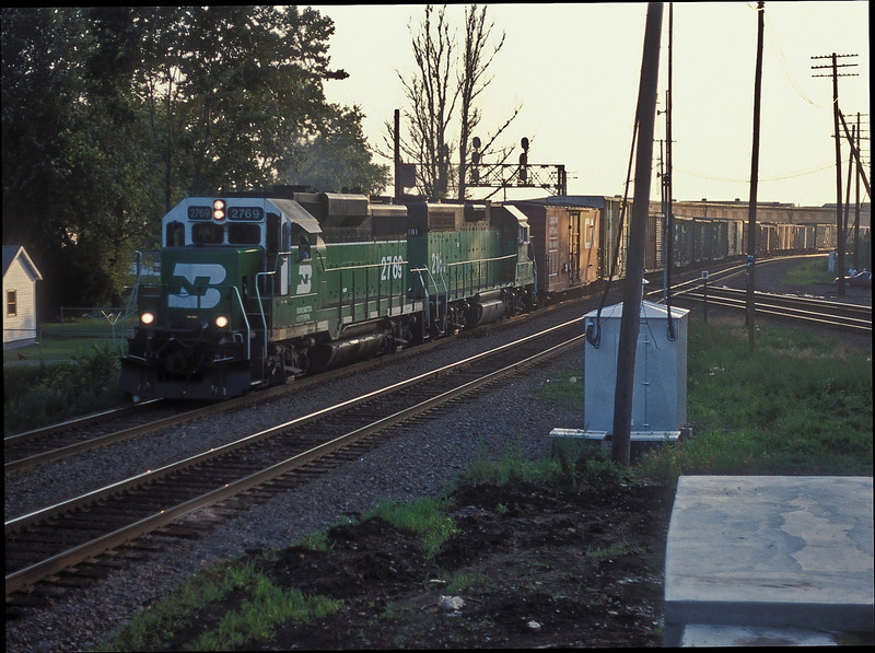 The evening sun has almost gone as BN GP39E 2769 and GP38X 2181 head back toward Chicago seen passing the Railfan platform at Rochelle on 7 July 1998