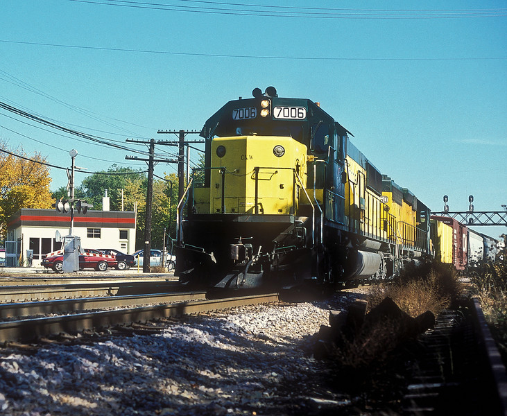 Chicago North Western SD50 7006 and SD40-2 6850 head west through West Chicago on 12 October 1994