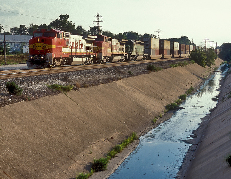 A double stack train passes through Galesburg on a sunny evening of 26 July 1998 with Santa Fe B40-8W 502 and 550 plus BN SD40-2 7856 on the front