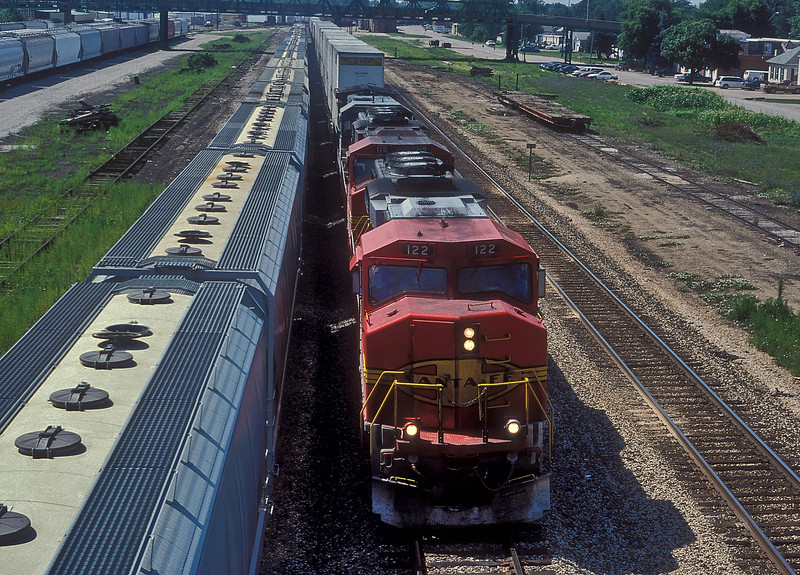 Heading toward Chicago, Santa Fe GP60M 122 and 119 plus LMXB39-8 8523 pass the yard at Streator which was full of empty hopper cars on 27 July 1998