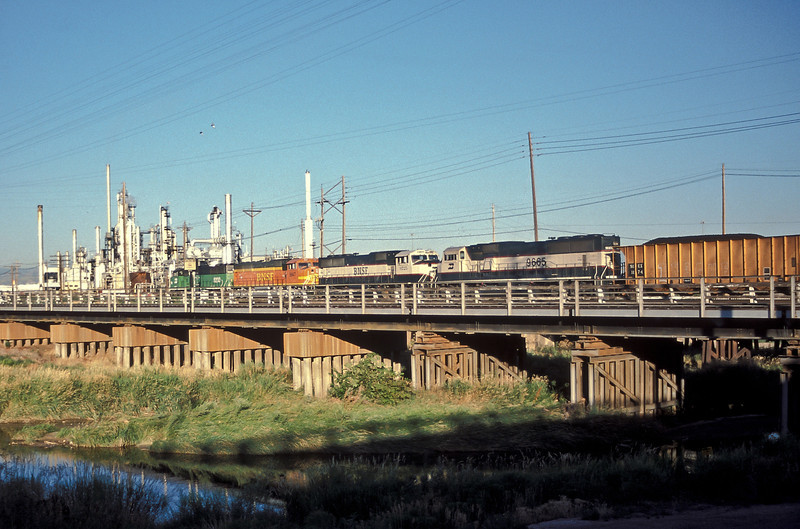 BN SD60M 9200 and three SD70MAC locos, 9947, 9725 and 9655, head a loaded coal train south into Denver seen passing Commerce City on 18 July 1998