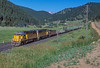 Union Pacific SD50 5082 and 5080 sweep through Rollins with a rail train on 16 July 1998 with some snow still visible on the Rockies in the background, even in high summer.