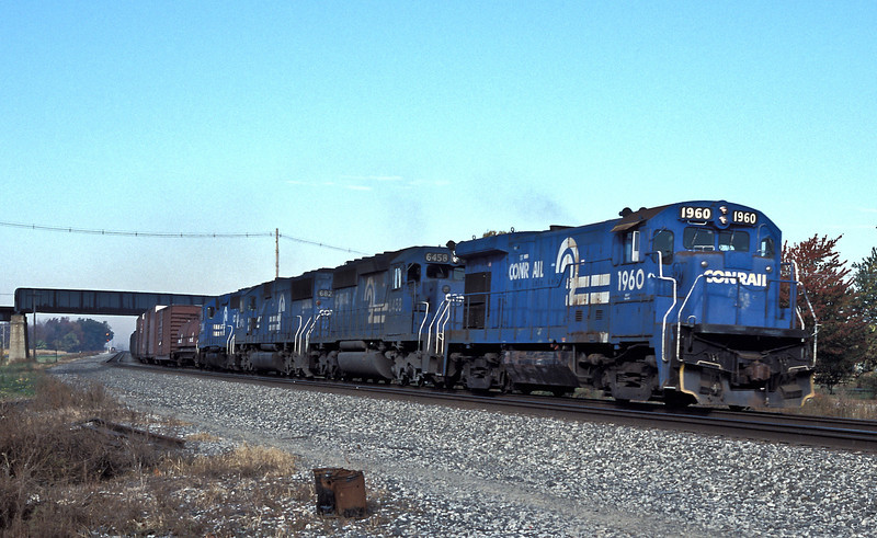 A Conrail eastbound heads through Oak Harbor headed by B23-7 1960, SD40-2 6458, SD50 6821 and GP40-2 3360 on 16 October 1994