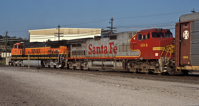 BNSF C44-9W 1112 and Santa Fe C44-9W 694 negotiate Santa Fe Junction in Kansas City on 20 July 1998 with empty car carriers