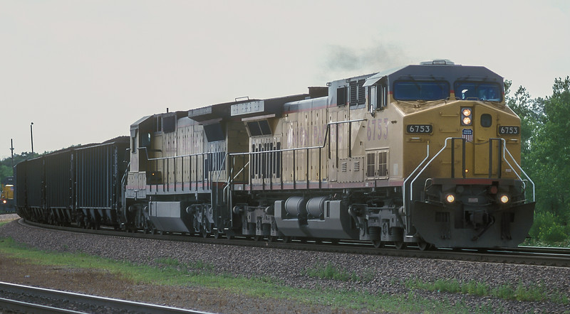 Union Pacific C44-9ACW 6753 and C40-8 9143 head a load of full Burlington Northern hoppers east through North Platte on 11 July 1998.