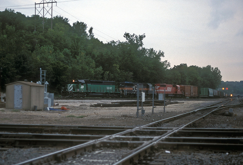 Late in the evening at Santa Fe Junction in Kansas City on 23 July 1998 BN SD40-2 6910 passes eastbound with HATX 500 (in Guilford paint) and SOO 771 in tow