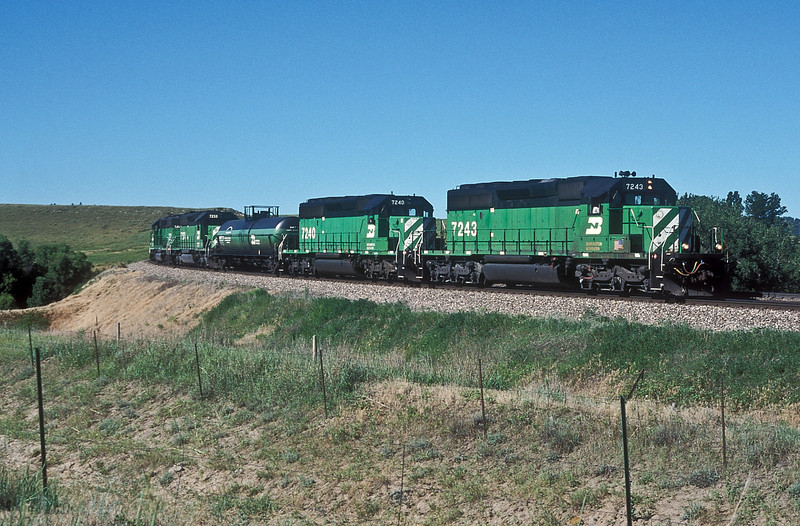 A Burlington Northern helper set formed of SD40-2 7243, 7240, 7233 and 7212 bracket an auxiluary fuel tanker that enables the locos to refuel while on the road as they drop down Craford Hill in Nebraska on 12 July 1998