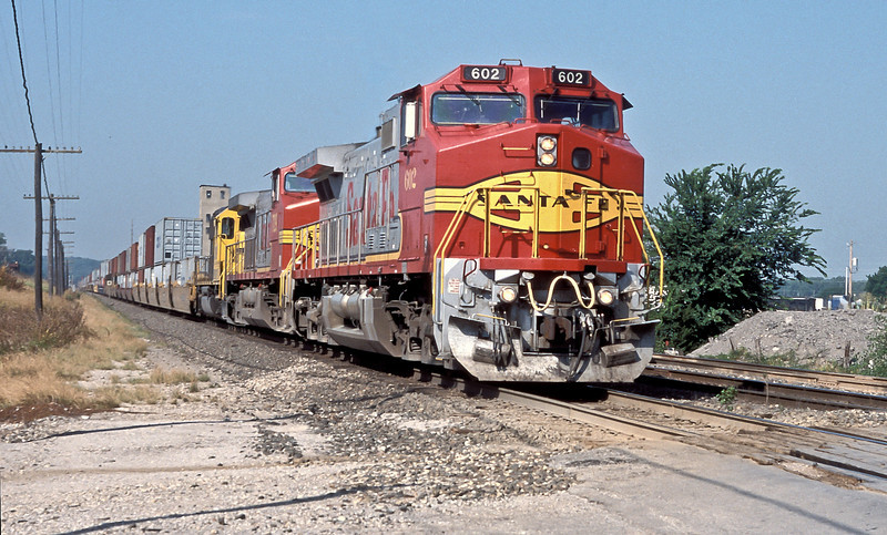 A westbound hurries through Holliday headed by Santa Fe C44-9W 602, sister GE 729 and patched BNSF GP50 3199 on 20 July 1998