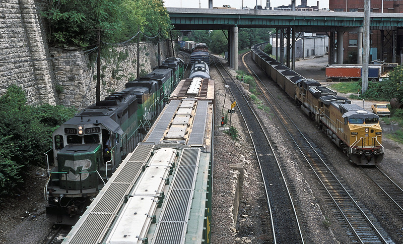 The area known as The Gooseneck in Kansas City can get busy at times. In this shot from 4th Street bridge on 22 July 1988 can be seen a set of light BN power comprising GP50 3131, B30-7A 4106 and 4049 and SD40-2 7126 heading back to Murray Yard passing a transfer freight from Murray to Argentine Yard. To the right can be seen a UP coal train headed for Neff Yard behind AC4400CW 7100 and SD9043AC 8061