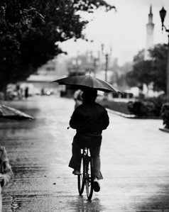Student riding a bike in the rain, University of Southern California, 1977