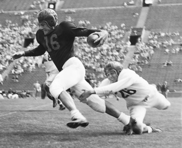 Frank Gifford freeing himself from tackling Johnny Williams in the final spring practice game, University of Southern California, 1957