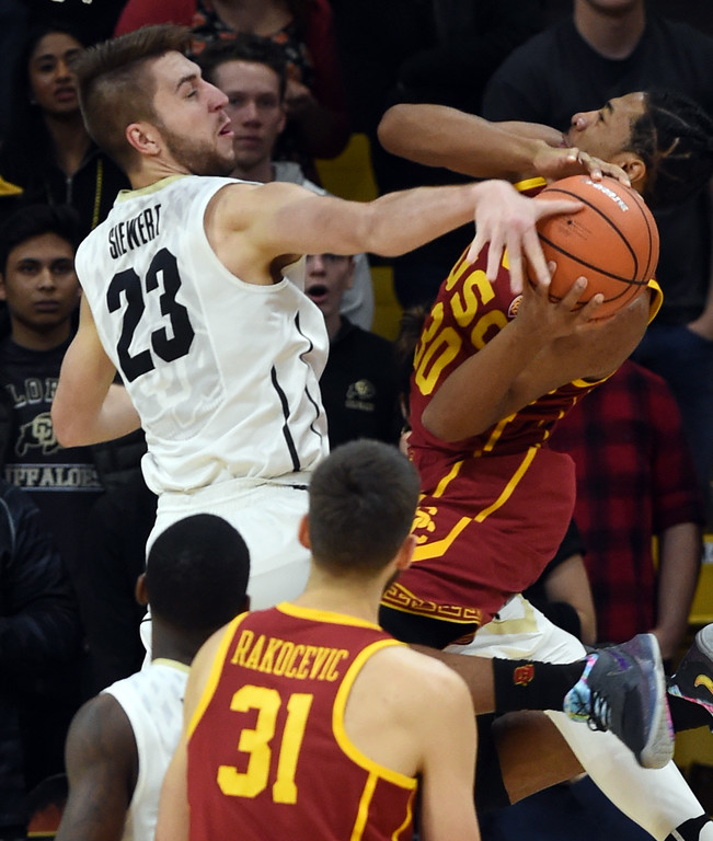 . Lucas Siewert, of CU, fouls Elijah Stewart, of USC.   Cliff Grassmick / Staff Photographer/ February 21, 2018