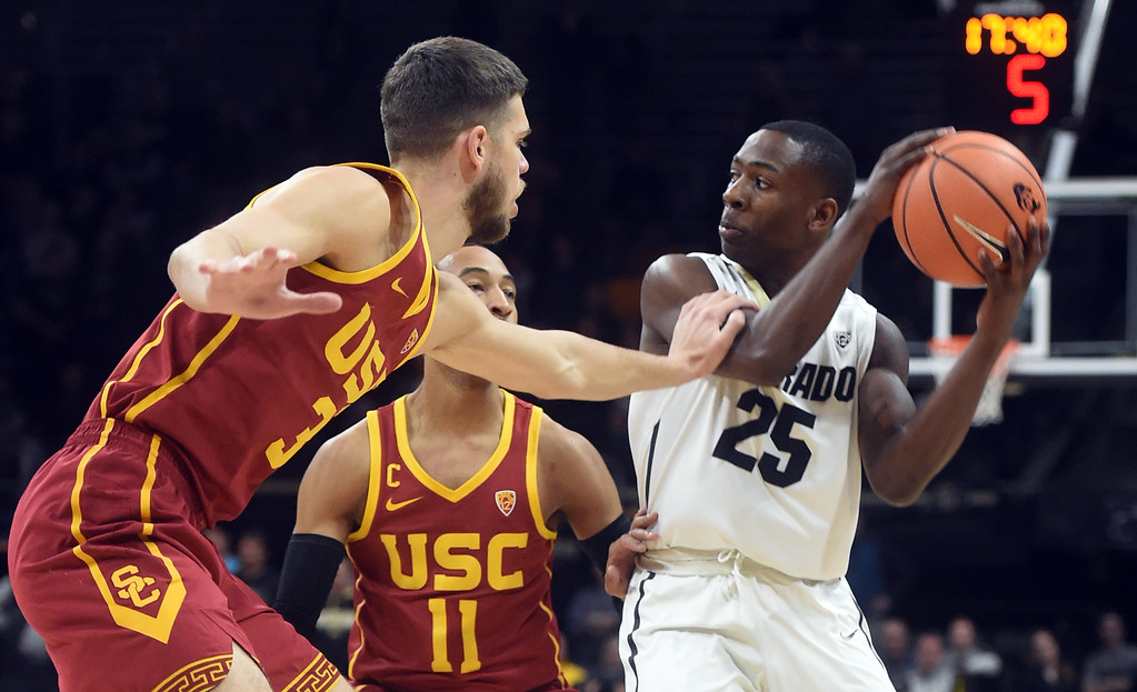 . Harrison Henderson, left, and Jordan McLaughlin, of USC, double McKinley Wright IV, of Colorado.   Cliff Grassmick / Staff Photographer/ February 21, 2018