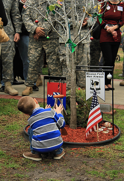 The son of CPL Luxmore, killed in Afghanistan in June 2012, plays with chimes someone placed at the memorial tree of his father on Ft. Stewart's Warriors Walk. 15 DEC 2012 marked the 6th Annual Wreaths for Warriors Walk ceremony commemorating the 447 Dog Face soldiers from 3rd INF DIV who died in war since 2001. <br /> <br /> The boy played for many minutes making music with the chimes for his daddy while a mesmerized crowd watched and cried.