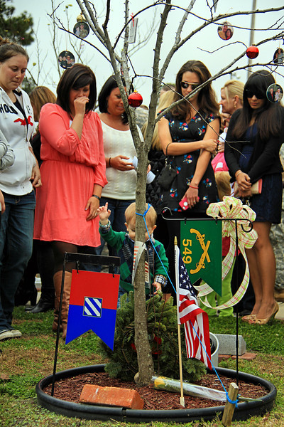 The family and widow of SGT Timothy Conrad look on as his son puts a dandelion on his dad's memorial at the Ft. Stewart Warriors Walk. The boy was just a baby when his dad was killed in Afghanistan in Feb 2012.<br /> <br /> 15 DEC 2012 marked the 6th annual Wreaths for Warriors Walk ceremony commemorating the fallen from 3rd INF DIV during the Christmas holiday season.