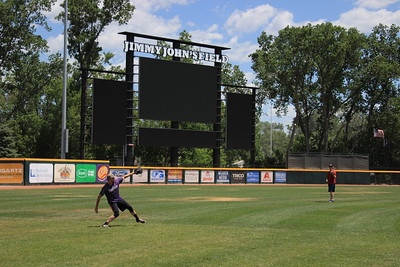 Athletes play catch in the outfield.