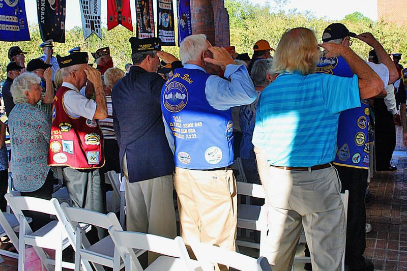 Veterans salute as the band plays America the Beautiful