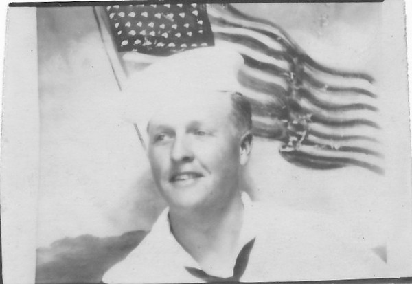 P00066 Sailor (Bill Edgar?) in dress whites against flag backdrop