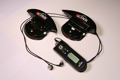 "The vLink system comprises three components: two ""shuttle"" pods, one mounted on each ski and a wireless system remote about the size of an MP3 player that controls the shuttles, receives data from them, displays performance measurements; and generates instant audible feedback on carving precision and velocity through a set of ear-buds. (Photo: Tom Kelly)"