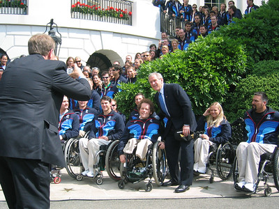 President Bush has a member of Congress help with photographs while meeting first-time Paralympian Tyler Walker (Franconia, NH) on May 17, 2006