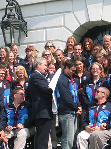President Bush autographs Torino posters for 2002 silver moguls medalist Shannon Bahrke (Tahoe City, CA) while two-time Olympian Jeremy Bloom (Loveland, CO) provides his back as an autograph table (May 17, 2006)