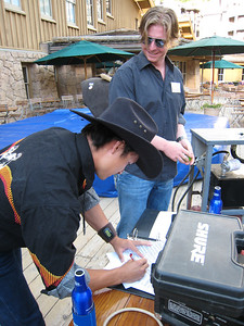 (l-r) Graham Watanabe and Nate Holland of U.S. Snowboarding signing the release forms before battling the mechanical bull (credit: Doug Haney/USSA)