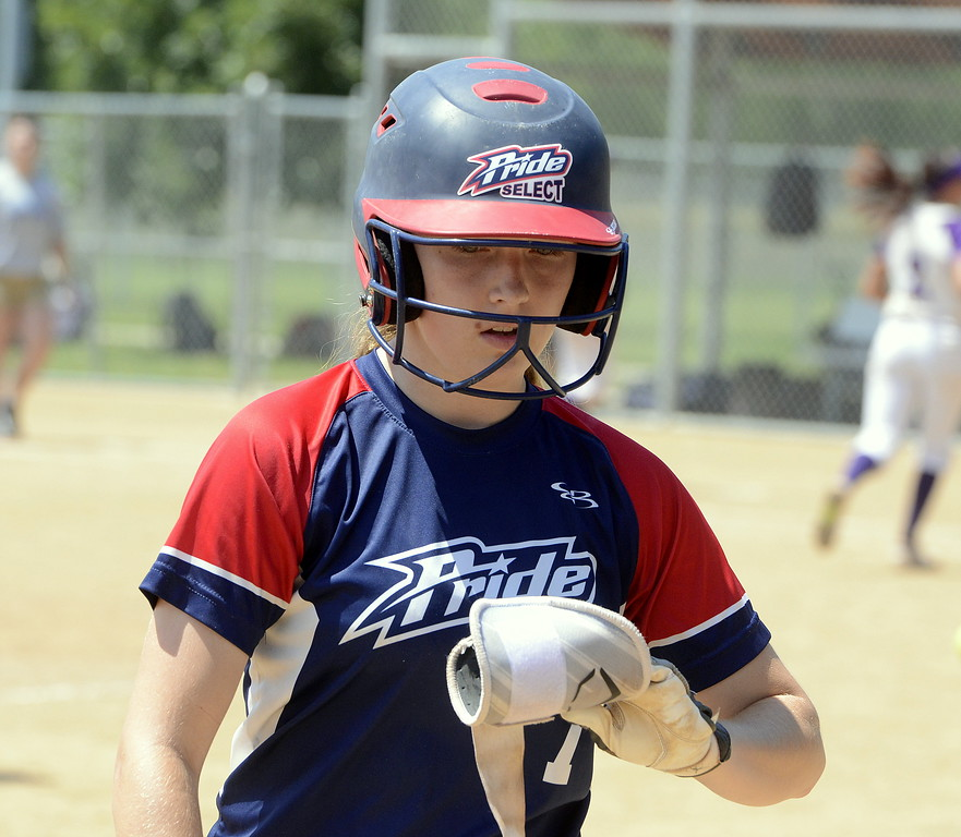 . Blaze Pride Elite\'s Tristan Pope removes her guard as she heads to the dugout at the end of an inning during Saturday\'s game with Evolution at the USSSA Mountain States Championships at the Barnes complex. (Mike Brohard/Loveland Reporter-Herald)