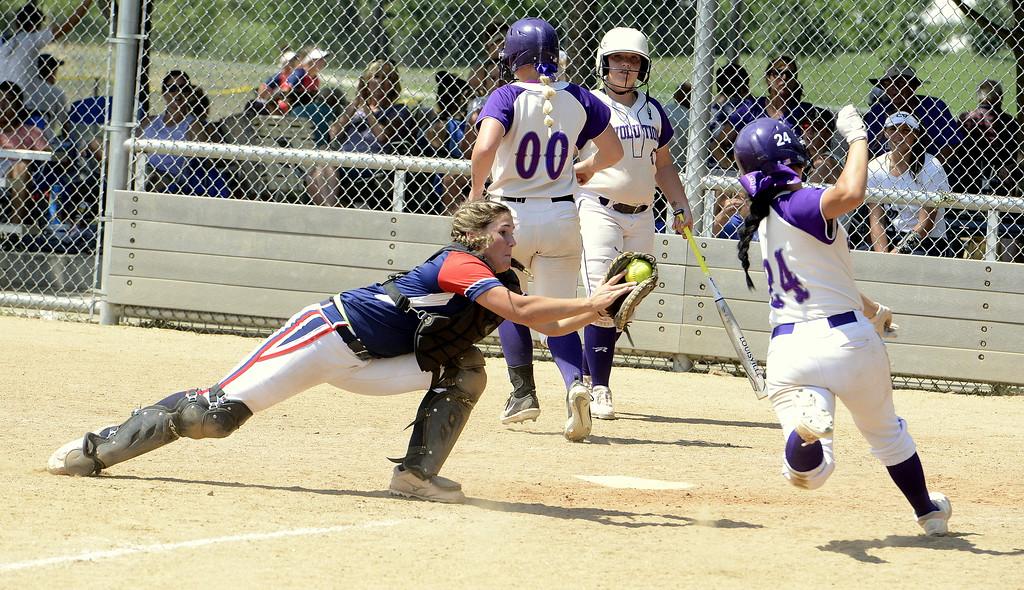 . Blaze Pride Elite catcher Marlee Hebda starts her dive to tag out Evolution\'s Mia Fernandes at the plate Saturday at the USSSA Mountain States Championships at the Barnes complex. (Mike Brohard/Loveland Reporter-Herald)