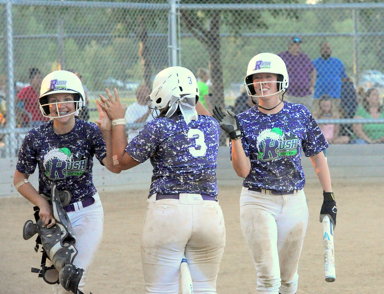 Rocky Mountain Rush teammates high five during the USSSA 16U B Mountain States Championship tournament at Barnes Complex in Loveland.