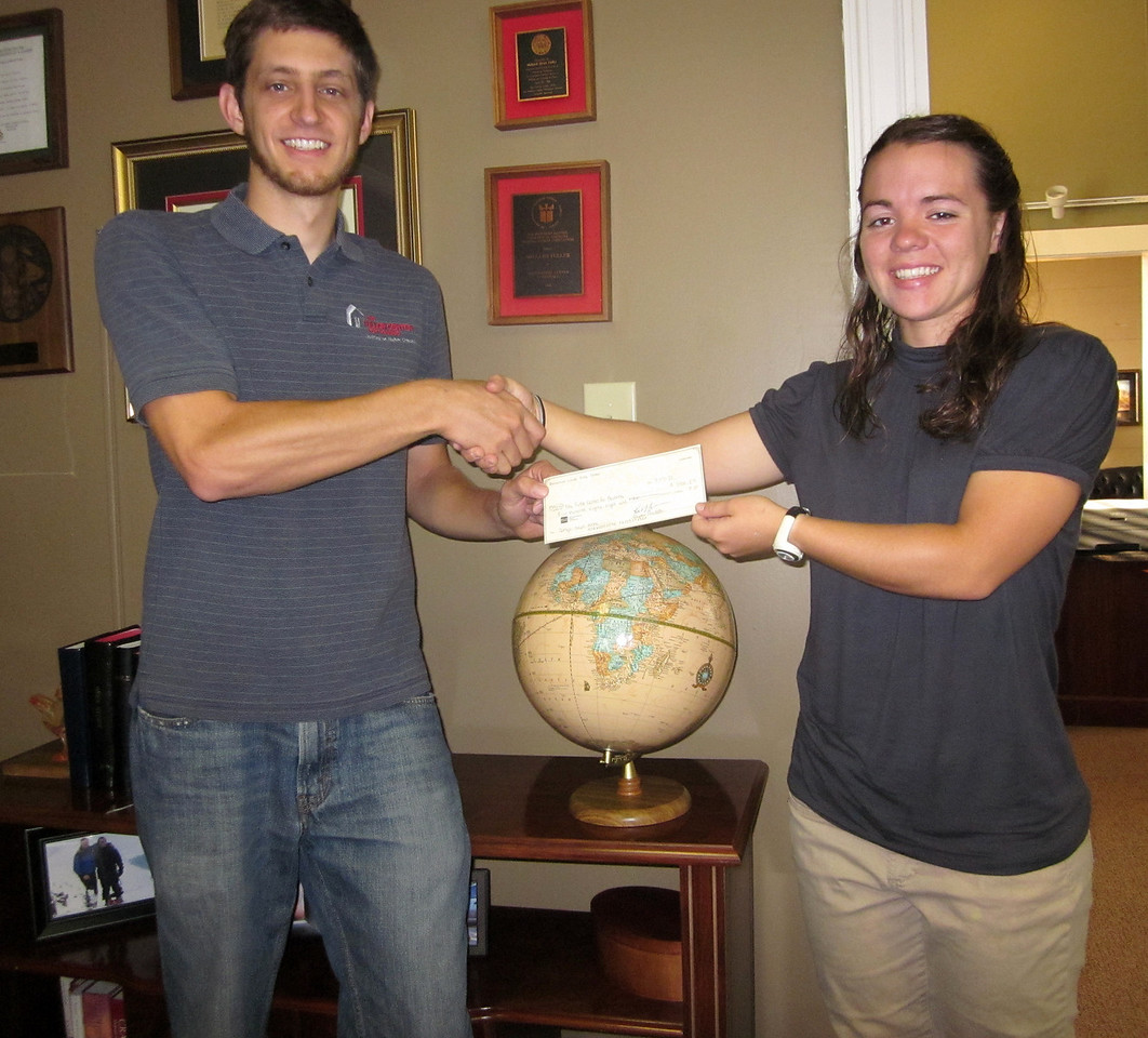Director of International Field Operations Ryan Iafigliola accepts a $588 check from new Americus-Sumter FCH Director Alyssa Hostetler on Sept. 15, 2011 -- the first tithe to The Fuller Center from Americus-Sumter under Alyssa's leadership. The two also took a peek at David Snell's globe, noting that this tithe is designated for work in the Democratic Republic of the Congo, which Ryan visited with a group in August 2011.