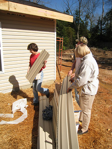 10 02-03  Cathy Smith of Fuller Center staff is helping with siding. ff